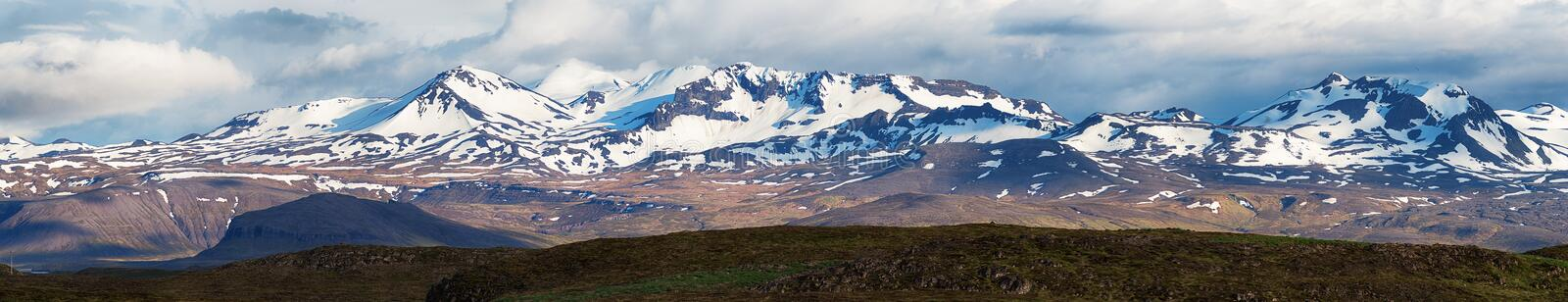 Mountain landscape in Iceland, panorama. Panoramic image of scenic snow clad mountains royalty free stock images