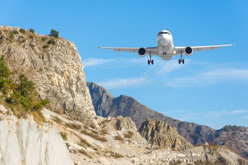 Mountain landscape and landing passenger aircraft. Travel to the mountainous countries.  stock photography
