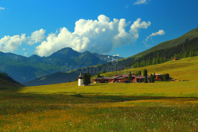 Mountain landscape with municipality of Sertig Dorfli. Summer mountain landscape with municipality of Sertig Dorfli, green meadow in the foreground, Davos royalty free stock photos