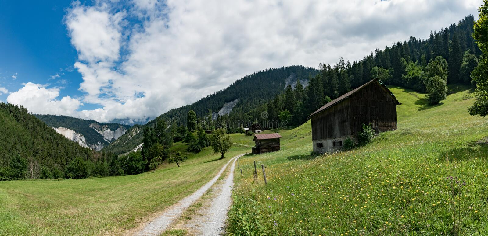 Mountain landscape with old wooden chalets and barns in summer in the Alps of Switzerland. Panorama mountain landscape with old wooden chalets and barns in royalty free stock photo
