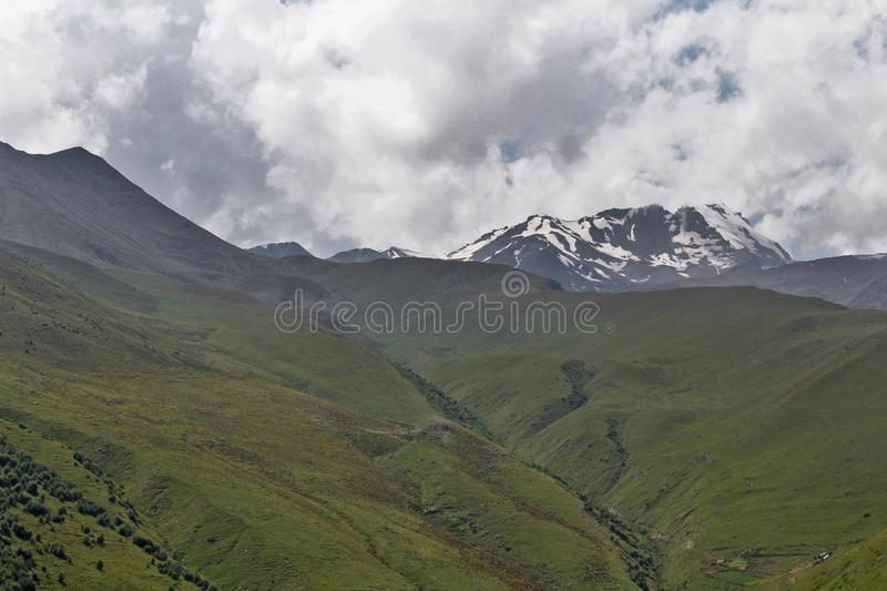 Mountain landscape with peaks of mountains covered with snow and clouds. Green slopes streaked with spring creeks royalty free stock photography