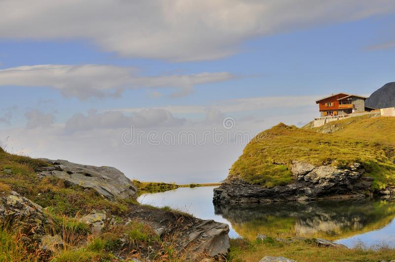 Mountain landscape with pond and chalet. Mountain lake Balea Lac with cabins and restaurants on the northside of the Fagaras mountains top view. The Bâlea stock photography