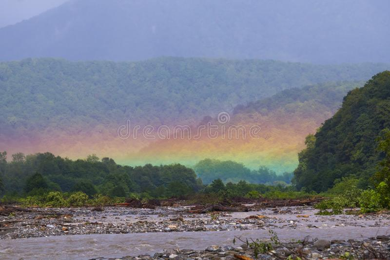 Mountain landscape with a rainbow over river. stock photo