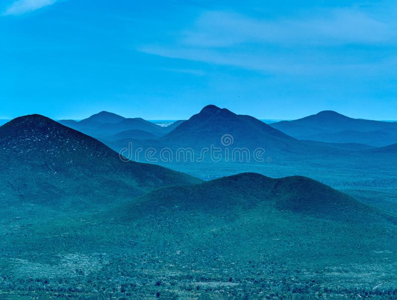 Mountain landscape Silhouette, layers of valleys and hills blue sky in background stock images