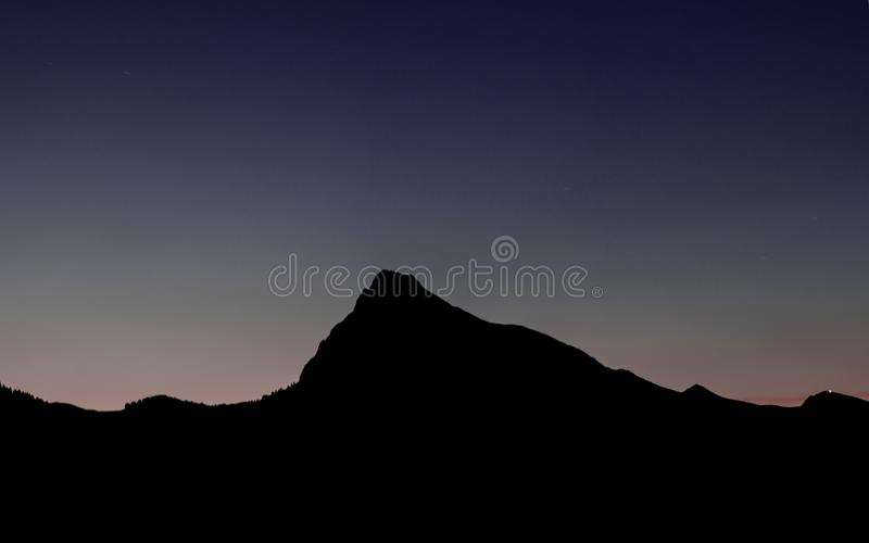 Mountain landscape silhouette under a late evening sky after sunset royalty free stock photo