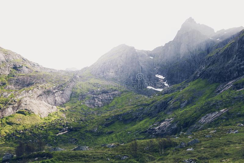 Mountains in Lofoten islands, Norway. Mountain landscape at summer in Lofoten, Norway. Vibrant image of shadow and light illuminating mountainside stock photo