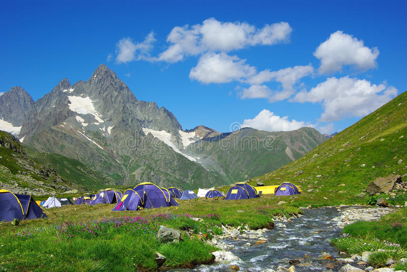 Mountain landscape with the tents. On the background of the blue sky royalty free stock image