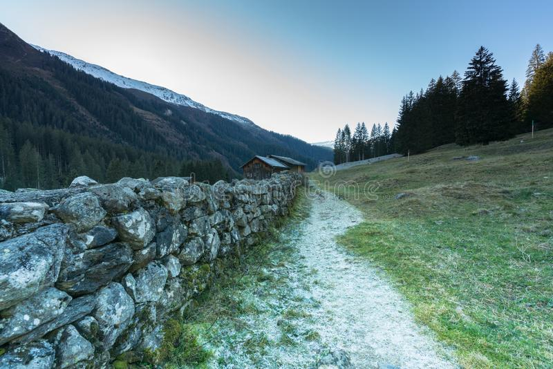 Mountain landscape and valley with forest and snow-capped mountain peaks and an old rock wall with wooden huts and chalets behind. In the Sardasca Valley near stock images