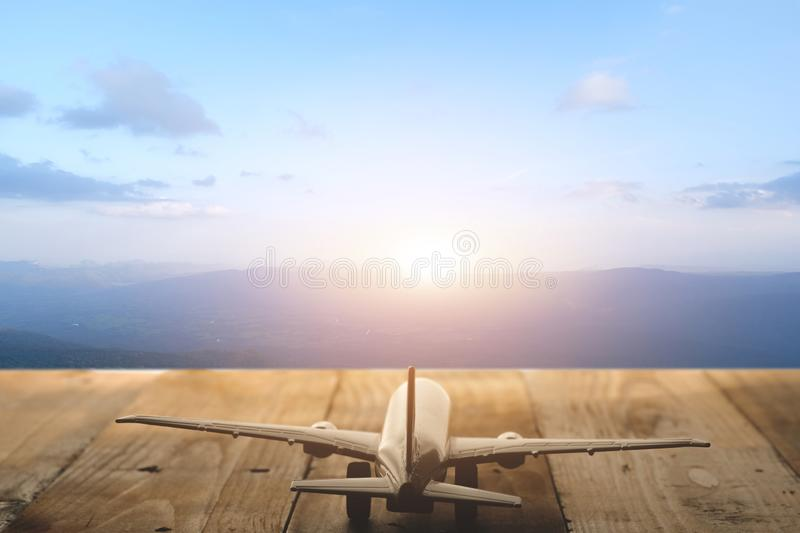 Mountain landscape with a view of the forest and white model of passenger plane on old wooden background. Travel saving and planning concept royalty free stock images