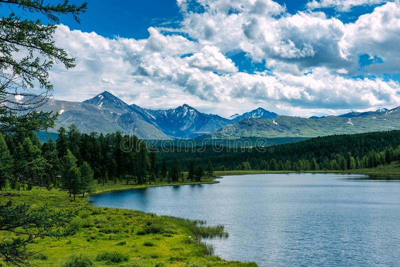 Mountain landscape, white clouds, lake and mountain range in the distance. Fantastic sunny day in mountains, large panorama. royalty free stock image
