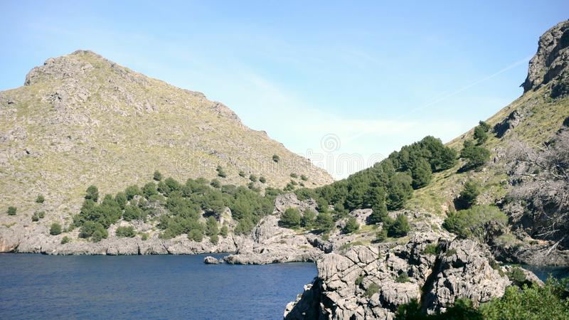 Mountain landscapes covered with green vegetation against blue sky. Art. Rocky cliff covered with trees and shrubs on. Shore with blue water at foot on clear stock photos