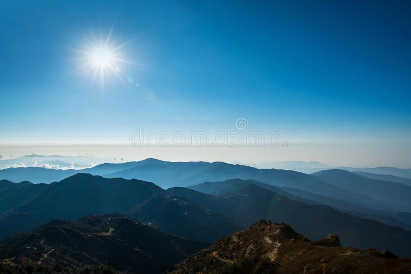 Mountain layer and sun on above blue sky landscape. View royalty free stock image