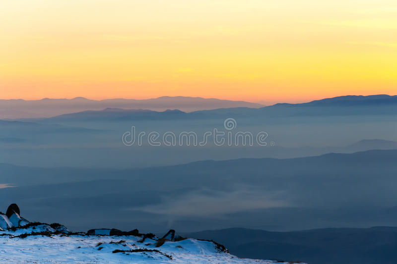 Mountain layers and colorful sunset in wintry mountain royalty free stock photos