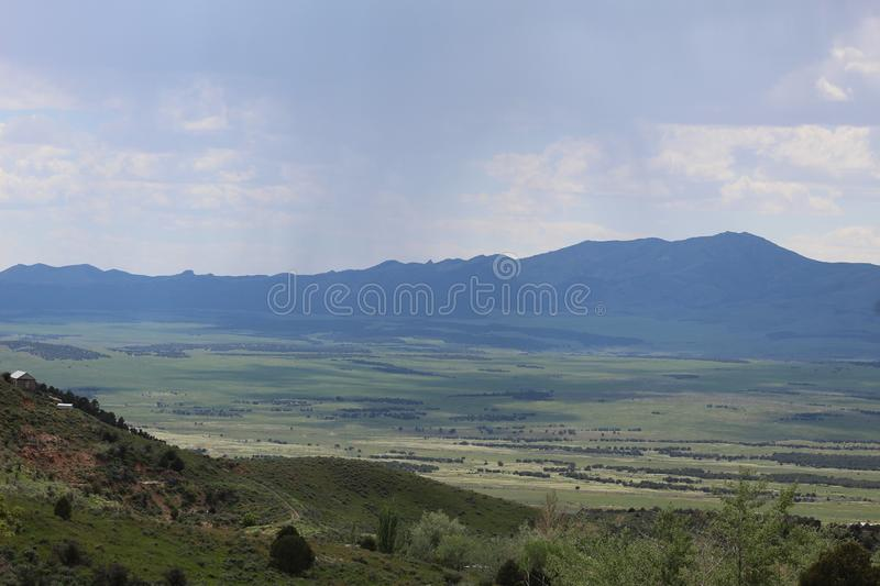 Mountain light sky coulds b. Light sky coulds mountain green for ground with bare ground in front of that with light sky coulds royalty free stock image