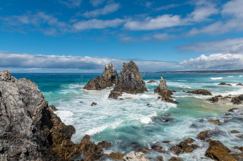 Camel Rock. Mountain-like rocky formations cover the beach as the waves of water come crashing in on a cloudy day in Camel Rock Australia stock photography