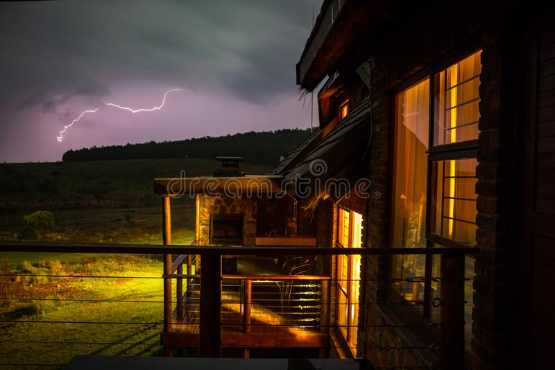 Mountain lodge with lightning in the background. Mountain lodge with purple lightning in the background stock images