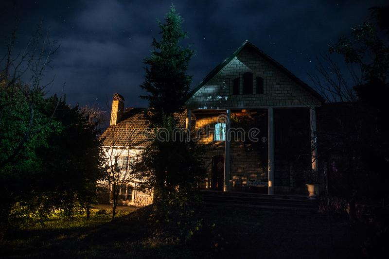 Mountain night landscape of building at forest at night with moon or vintage country house at night with clouds and stars. Summer. Night. Photo taken with long stock photography