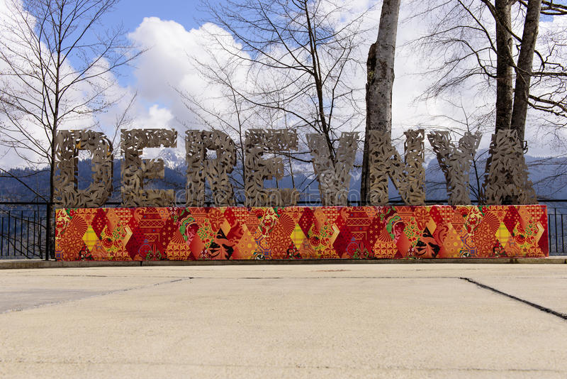 The mountain Olympic village. SOCHI, RUSSIA - MAY 2: The inscription in large letters DEREVNYA in the mountain Olympic village resort Rosa Khutor - the place of royalty free stock photography