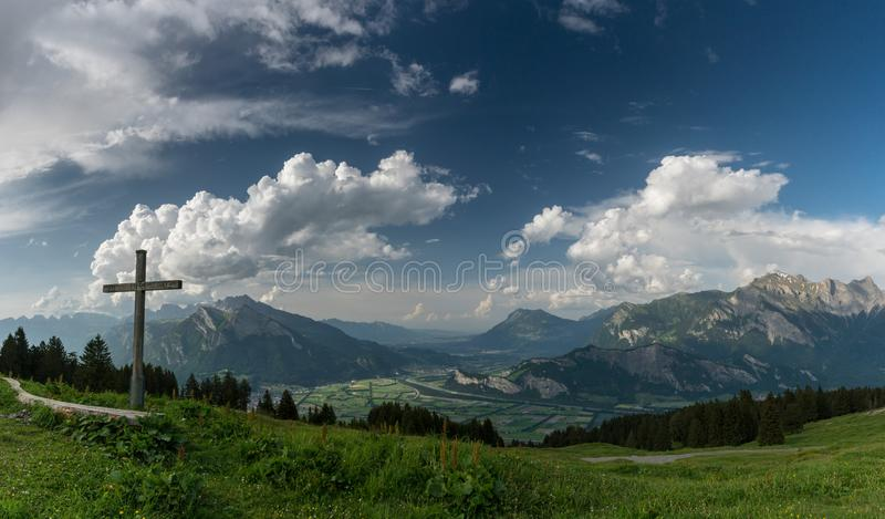 Mountain panorama with a gorgeous view of the Swiss Alps and Valleys and a summit cross royalty free stock photography