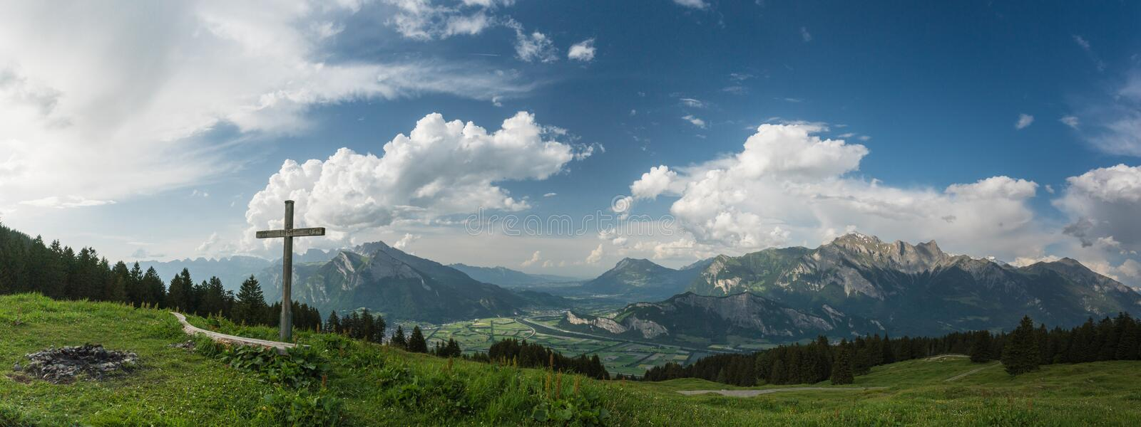 Mountain panorama with a gorgeous view of the Swiss Alps and Valleys and a summit cross stock photos