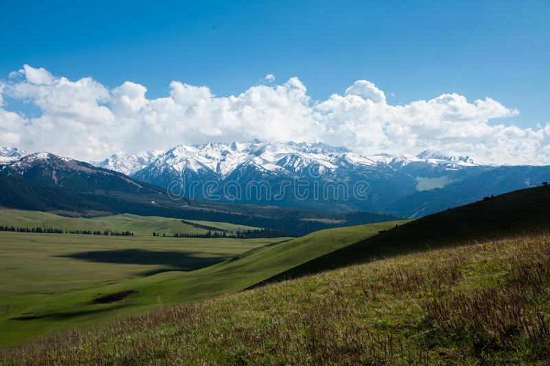 Mountain panorama with green field and blue sky stock photos