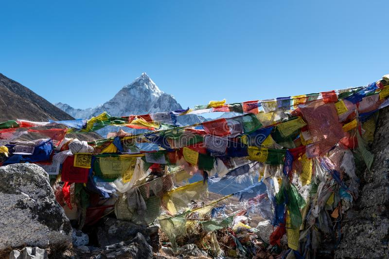 Mountain peak above prayer flags in the Himalayan mountains royalty free stock photo