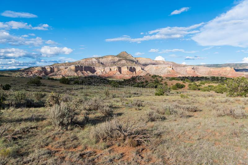 Colorful mountain peak and cliffs rise above a grassy sagebrush covered plain in New Mexico. Mountain peak, colorful cliffs, and vast desert landscape underneath royalty free stock photography