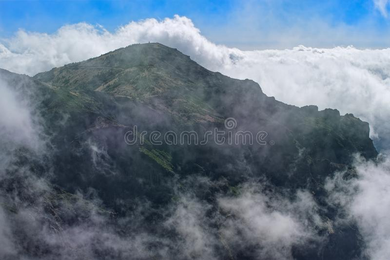 Mountain peak in dense clouds against blue sky. Madeira island. Mountain peak in dense clouds against blue sky. View from Pico do Arieiro on Portuguese island of stock photos