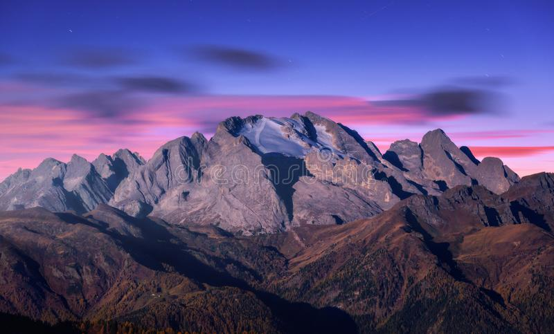 Mountain peak lighted by moonlight in autumn at night. In Dolomites, Italy. Beautiful landscape with mountains, forest on hills, purple sky with pink clouds royalty free stock image