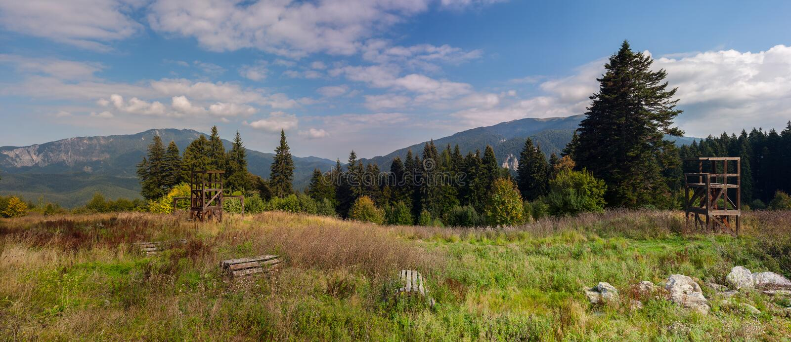 Mountain peaks in bright sunlight. Wooden constructions for training on a meadow royalty free stock images