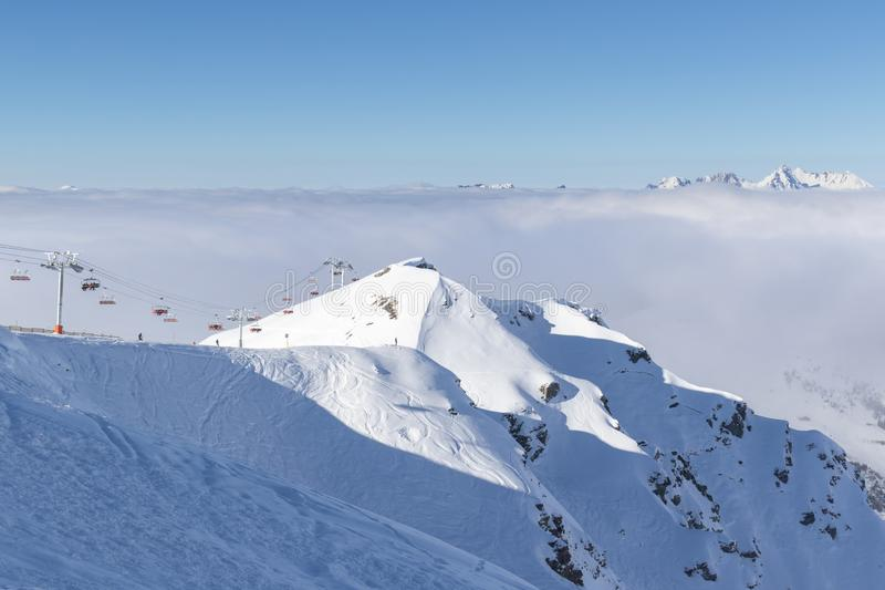 Mountain peaks covered in snow above clouds in La Plagne, French Savoy Alps royalty free stock image