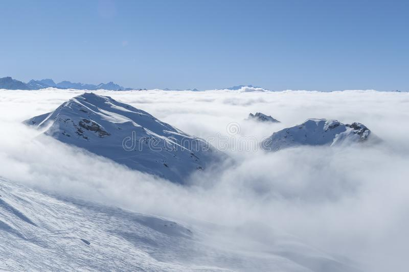Mountain peaks covered in snow above clouds in La Plagne, French Savoy Alps. Winter scenic scenery royalty free stock images