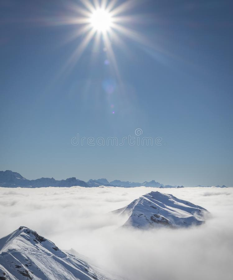 Mountain peaks covered in snow above clouds in La Plagne, French Savoy Alps. Winter scenic scenery, blue sky and stunning views royalty free stock photos