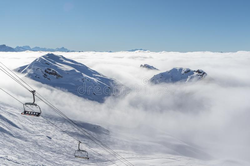 Mountain peaks covered in snow above clouds in La Plagne, French Savoy Alps. Winter scenic scenery, blue sky and stunning views. stock photo