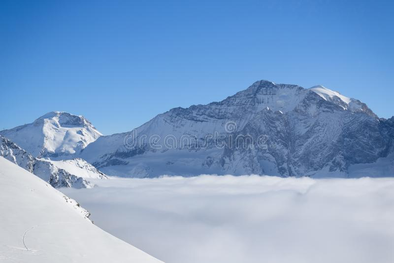 Mountain peaks covered in snow above clouds in La Plagne, French Savoy Alps. Winter scenic scenery stock images