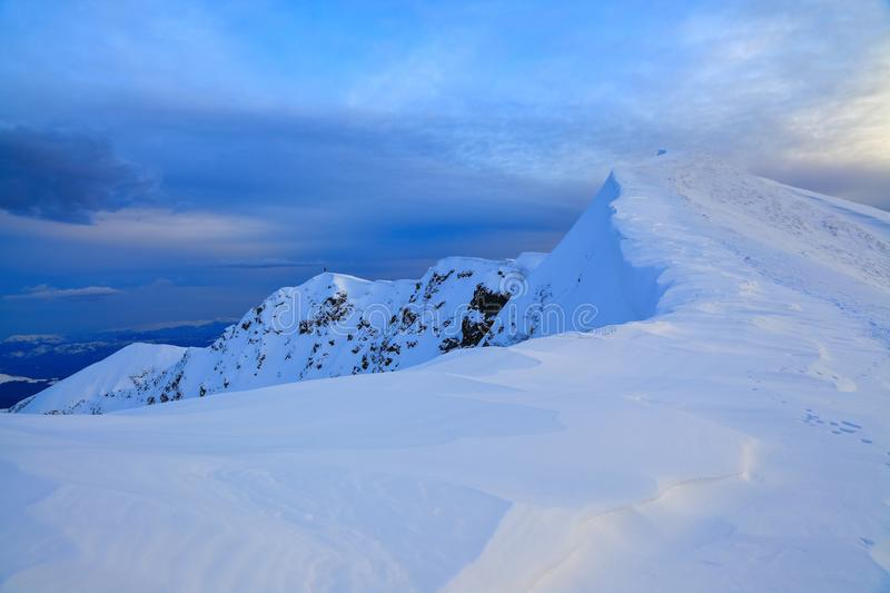 Mountain peaks covered with snow and ice, on which falls blue shadow, against the sky covered with fluffy clouds. Fantastic winter scenery stock photo