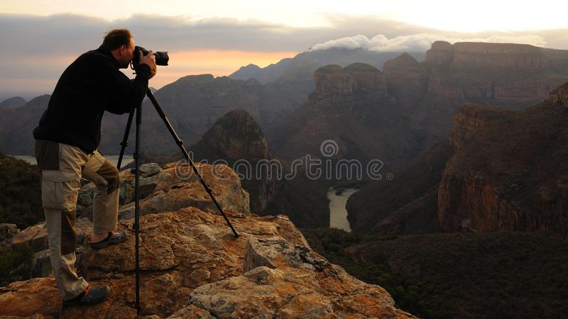 Mountain Photographer. This photographer takes a photo from the Three Rondavels in the Blyde River Canyon in South Africa stock photography