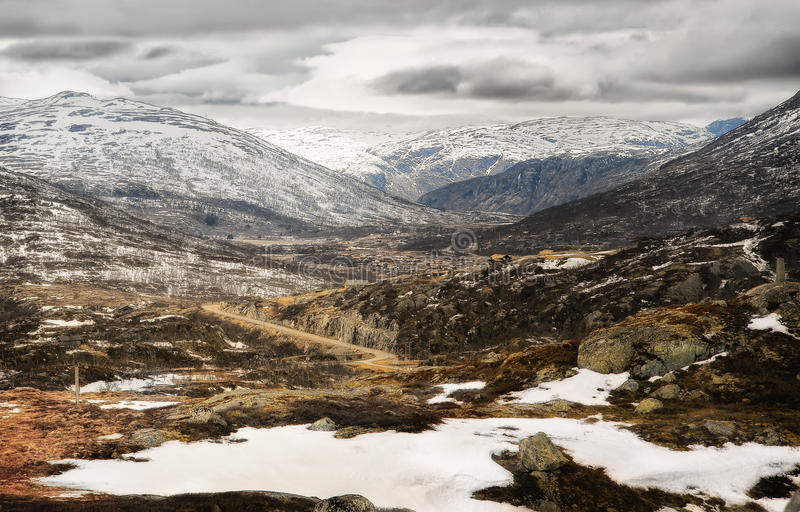 Mountain Plateau, Norway. Trees and rock emerge from the stark early spring snowy landscape of the Hardangervidda Mountain Plateau, Europe's largest mountain royalty free stock photo