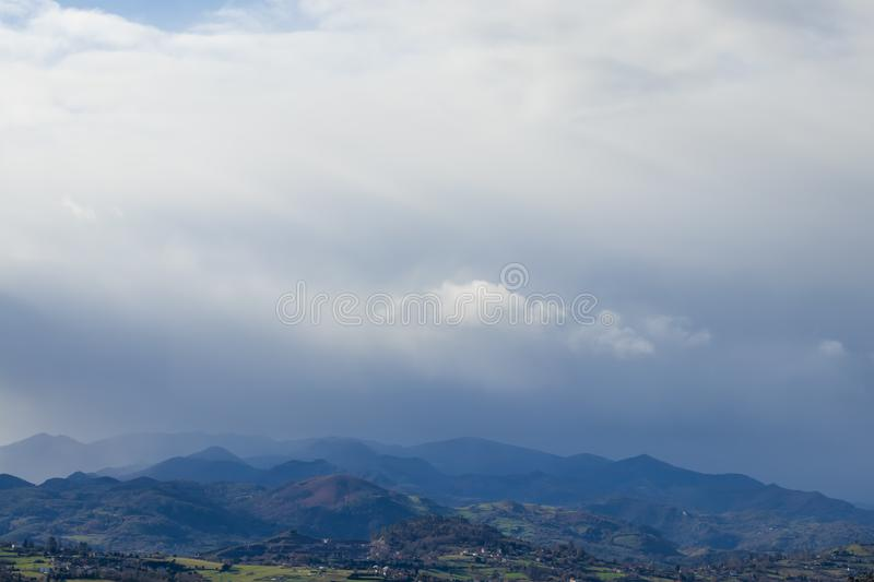 Mountain range in clear weather in contrasting rain clouds before the rain royalty free stock photography