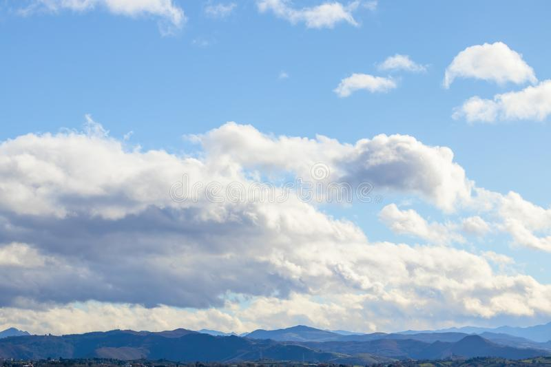 Mountain range in clear weather in contrasting rain clouds before the rain stock photo
