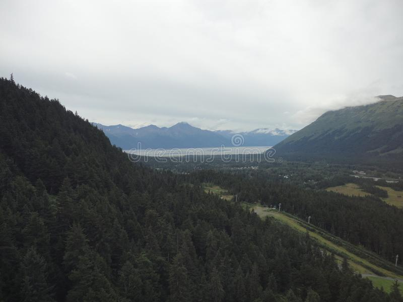Mountain Range with Forests and Stream. Lush temperate rainforest in alaska with clouds and sun stock photography