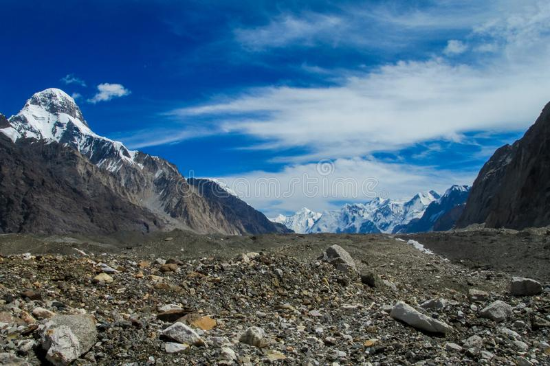 Mountain range snow peaks above glacier covered with gray stones royalty free stock images