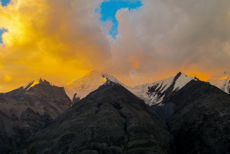 Mountain range snow peaks under orange sunset clouds stock photography