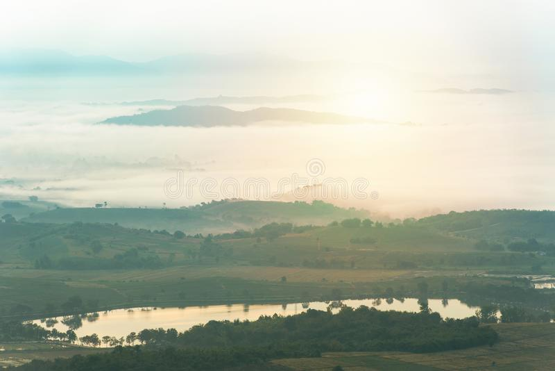 Mountain range with visible silhouettes through the morning colorful fog over pond water.  stock photos