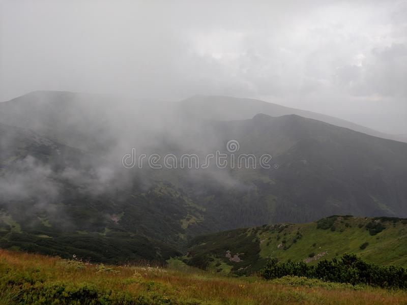 Mountain ranges in cloudy weather near the lake. Nature royalty free stock image