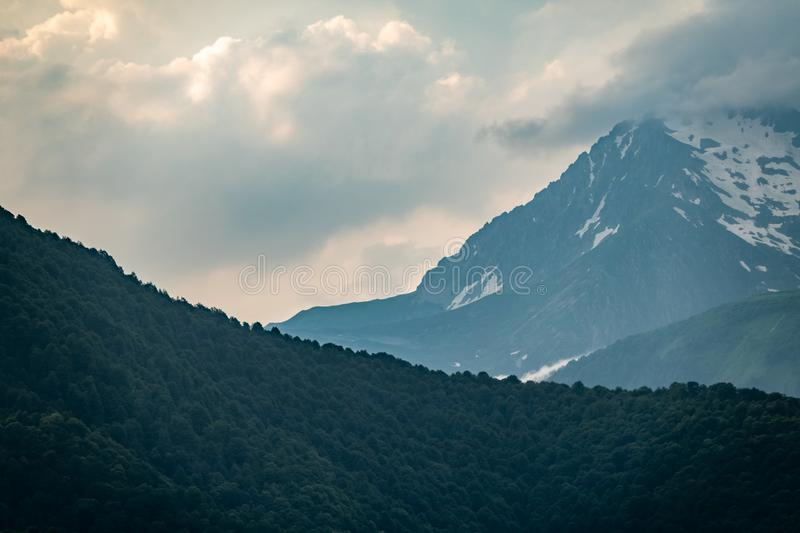Mountain ranges with green and rocky slopes. Mountains with snowy peaks hidden in the clouds royalty free stock image