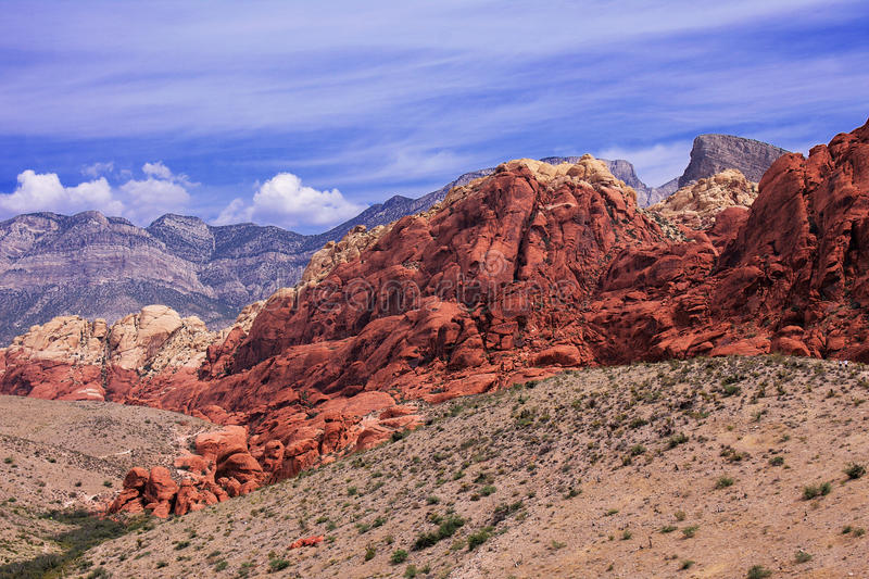 Mountain ranges in Red Rock, Nevada. The rocks are vivid red, orange and dark brown, and show signs of heavy erosion. The sky is b royalty free stock images