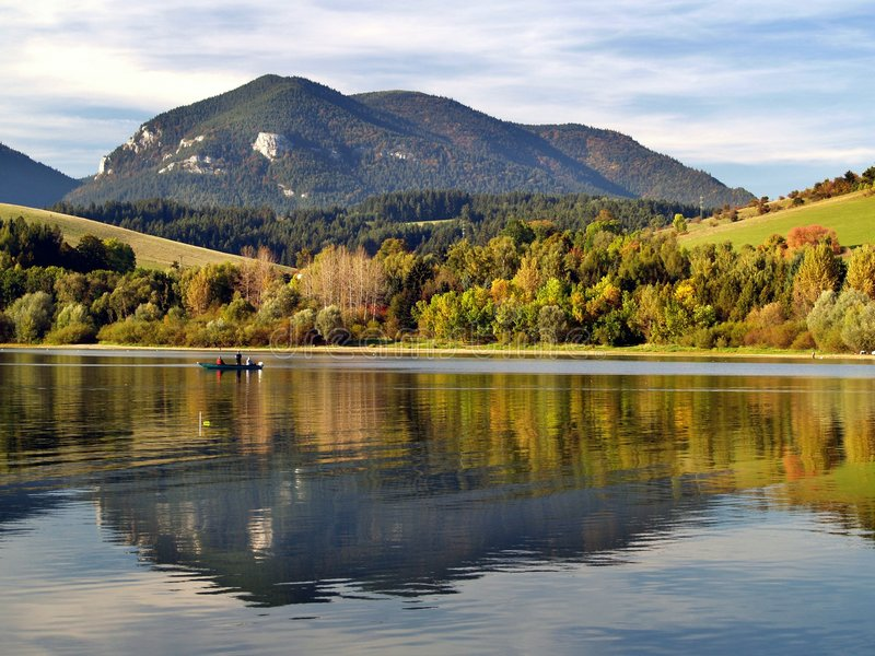 Mountain reflected in lake. Scenic view of mountain and forest reflected in lake stock images