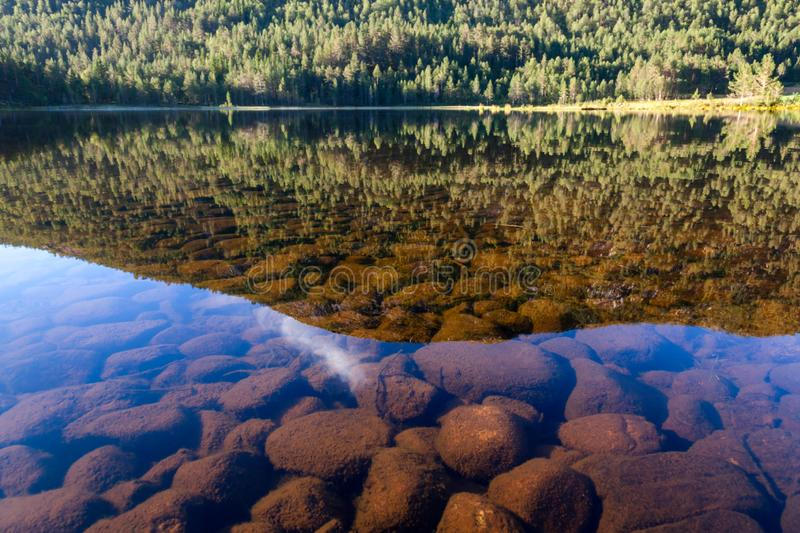 Crystal clear mountain lake in Telemark County Norway. Mountain reflecting in the calm water of Norwegian crystal clear lake with rocky bottom in Telemark County stock image