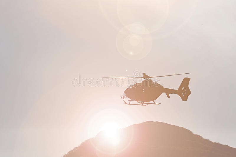 Mountain rescue helicopter. Against the sun in the mountains royalty free stock photos